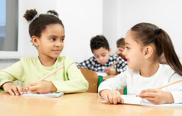 Ragazze allo scrittorio in aula, guardandosi l'un l'altro, in posa.
