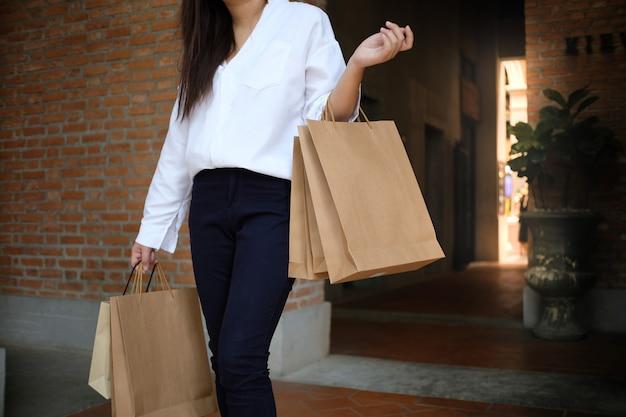 Ragazze asiatiche che tengono i sacchetti della spesa di vendita. concetto di stile di vita di consumismo nel centro commerciale.