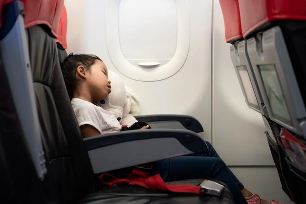 Ragazze asiatiche che viaggiano in aereo. lei abbraccia la sua bambola e dorme