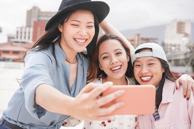 Ragazze asiatiche d'avanguardia che realizzano video storie per l'app di social network all'aperto. amici delle giovani donne divertendosi prendendo selfie