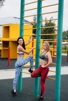 Ragazze atletiche e sexy praticano sport all'aria aperta. fitness, stile di vita sano.