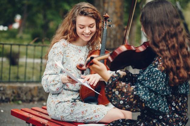 Ragazze belle e romantiche in un parco con un violino