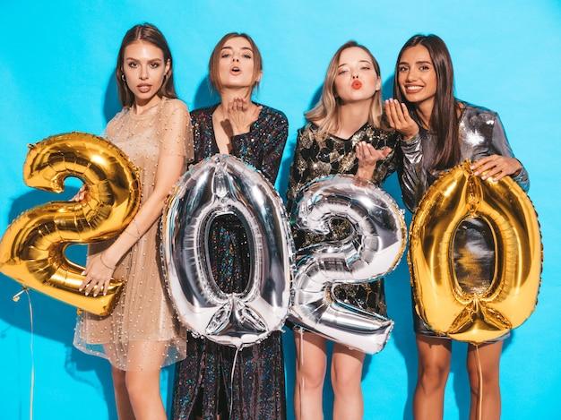 Ragazze bellissime felici in eleganti abiti da festa sexy con palloncini oro e argento 2020