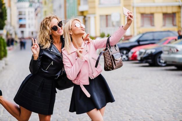 Ragazze bionde in piedi sulla strada makingie selfie