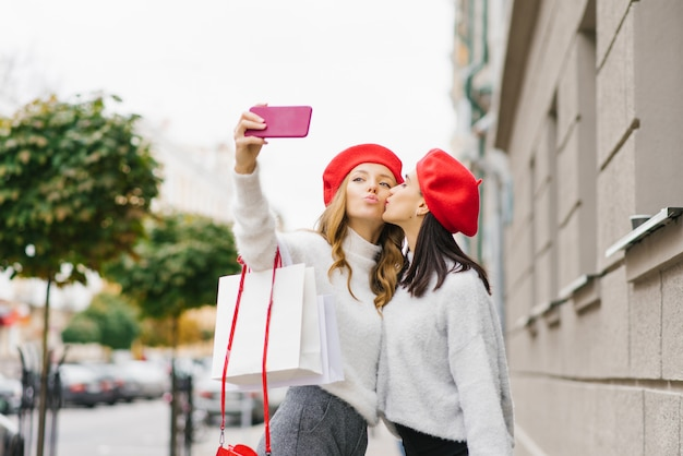 Ragazze carine brillanti in berretti rossi e maglioni leggeri fanno un selfie al telefono