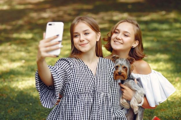 Ragazze carine in un parco giocando con cagnolino
