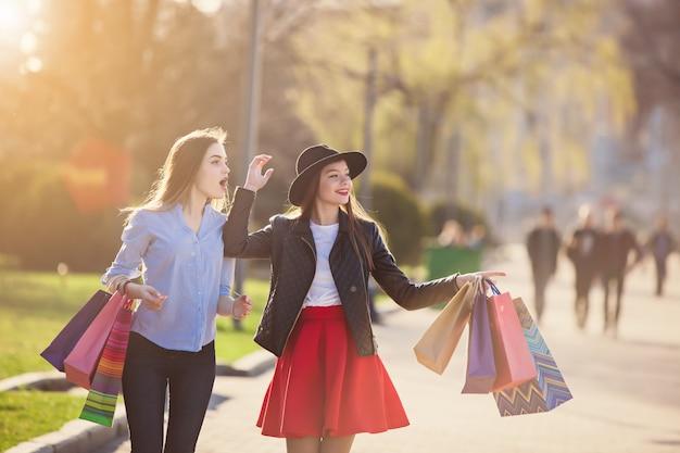 Ragazze che camminano con lo shopping per le strade della città