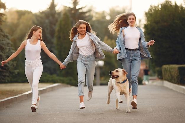 Ragazze che camminano in una città di primavera con cane carino