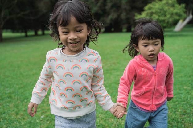 Ragazze che corrono insieme e che tengono mano nel parco