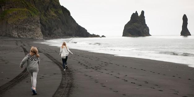 Ragazze che corrono sulla spiaggia di sabbia vulcanica nera con tracce di pneumatici e impronte, scogliere