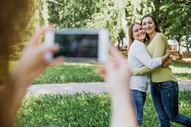 Ragazze che fotografano mentre abbracciano