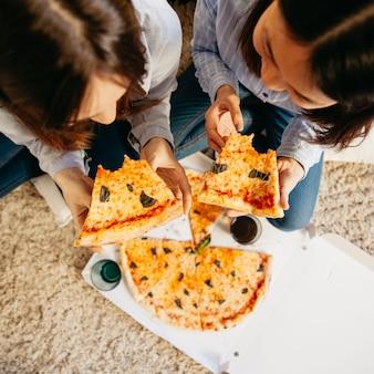 Ragazze che mangiano pizza sul pavimento