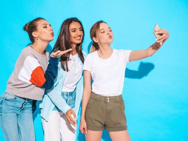 Ragazze che prendono le foto dell'autoritratto del selfie sullo smartphone modelli che posano vicino alla parete blu in studio femmina che fa il fronte dell'anatra sulla macchina fotografica frontale