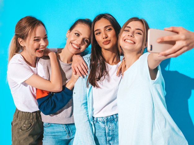 Ragazze che prendono le foto dell'autoritratto del selfie sullo smartphone modelli che posano vicino alla parete blu in studio, femmina che mostra le emozioni positive del fronte