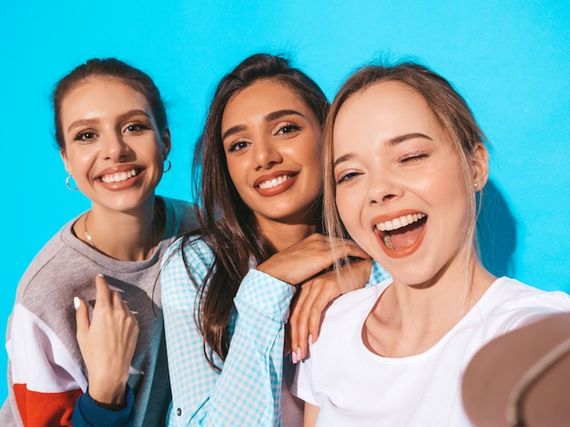 Ragazze che prendono le foto dell'autoritratto del selfie sullo smartphone modelli che posano vicino alla parete blu in studio.