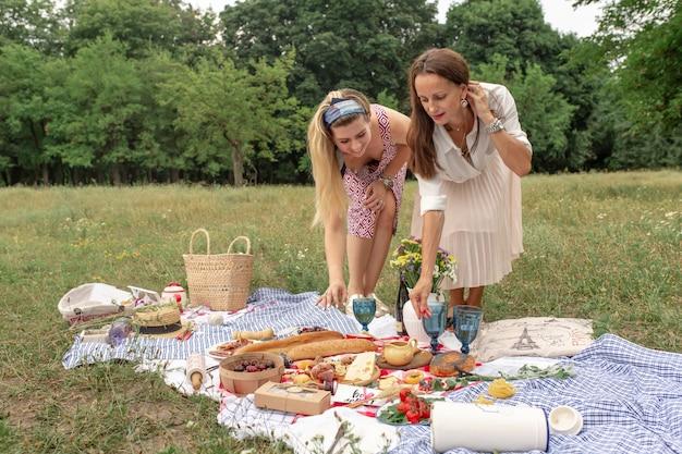 Ragazze che presentano cibo da picnic su una coperta da picnic a scacchi