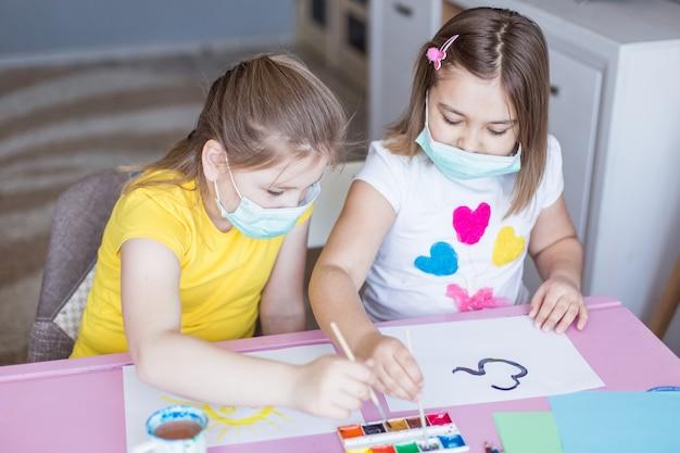 Ragazze che riuniscono a casa durante la quarantena in maschere sterili. giochi per l'infanzia, arte del disegno, concetto di stare a casa