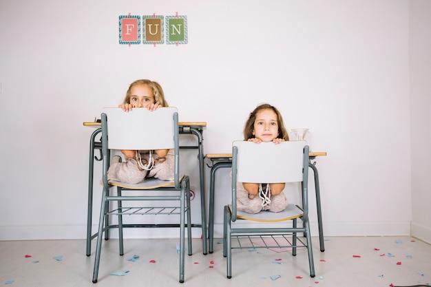 Ragazze che sbirciano da dietro le schiene delle sedie