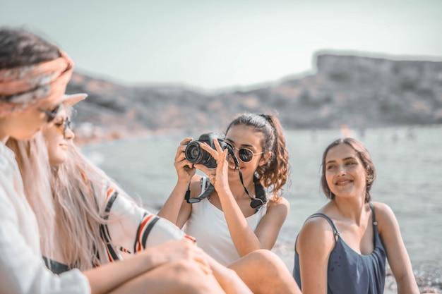 Ragazze che scattano foto sulla spiaggia
