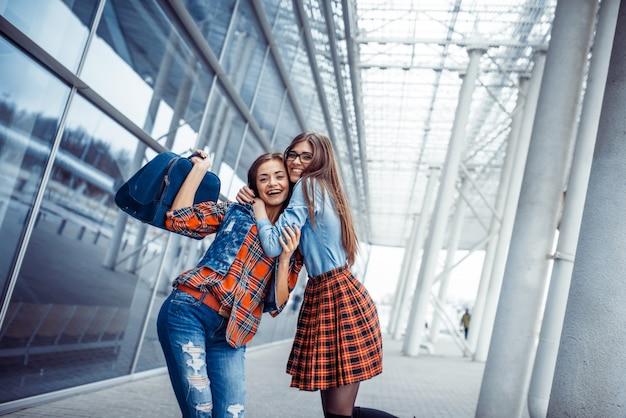 Ragazze che si divertono e felici quando si incontrano in aeroporto.