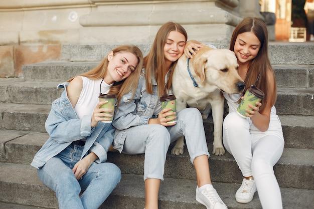 Ragazze che si siedono su una scala con cane carino