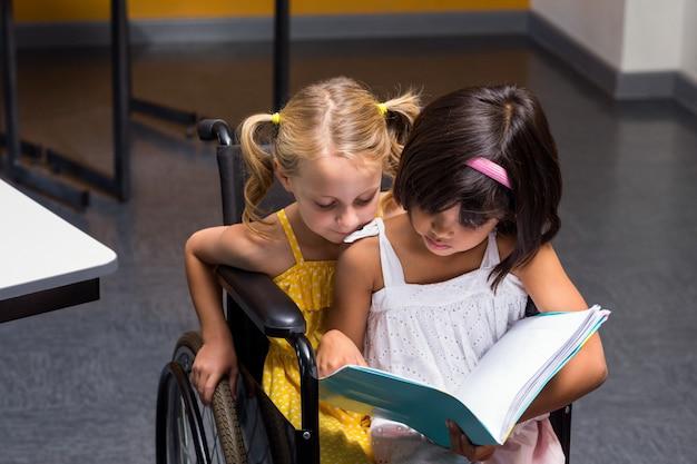 Ragazze che si siedono sul libro di lettura della sedia a rotelle