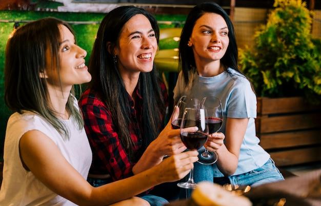 Ragazze che sorridono alla tostatura del vino alla festa
