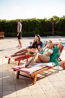 Ragazze che sorridono, facendo selfie, sdraiati sulle sedie vicino alla piscina