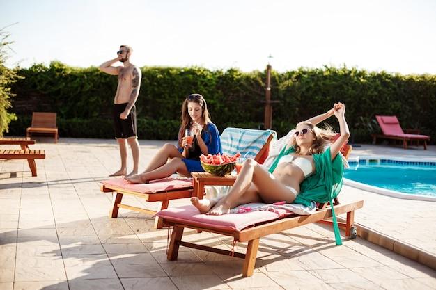 Ragazze che sorridono, prendere il sole, sdraiati su sedie a sdraio vicino alla piscina
