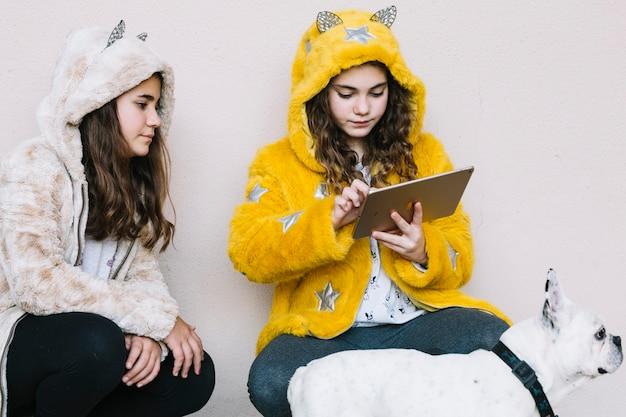 Ragazze con cane guardando tablet