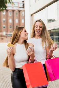 Ragazze con i sacchetti della spesa che camminano per la strada