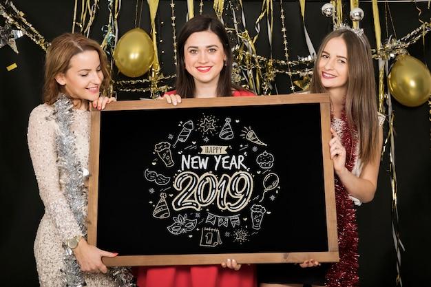 Ragazze con la lavagna al nuovo anno 2019 partito