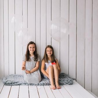 Ragazze con palloncini seduti sulla coperta