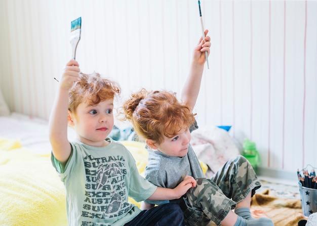 Ragazze con spazzole in mani alzate seduto sul pavimento