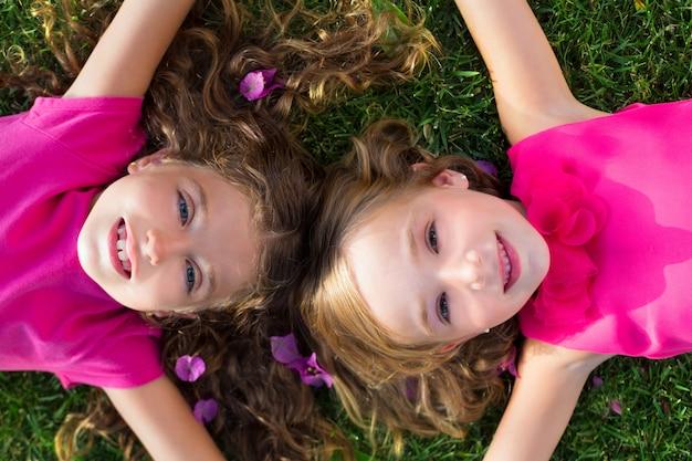 Ragazze degli amici dei bambini che si trovano sull'erba del giardino che sorride