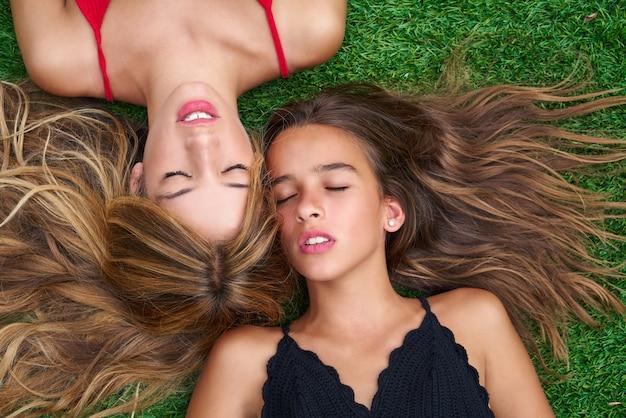 Ragazze degli migliori amici dell'adolescente che si trovano giù su tappeto erboso