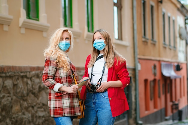Ragazze dei turisti che indossano le maschere per il viso in strada.