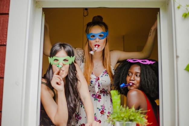 Ragazze del partito che presentano alla finestra