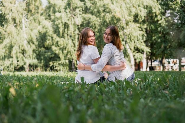 Ragazze dell'adolescente che abbracciano e che esaminano macchina fotografica