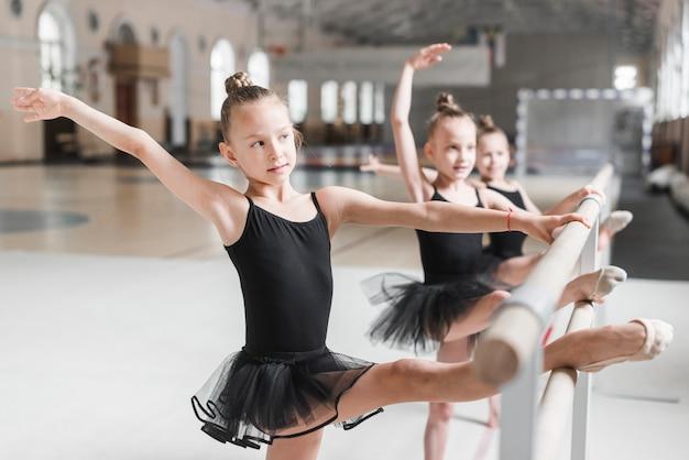 Ragazze della ballerina in tutu nero che allunga le loro gambe sulla barra