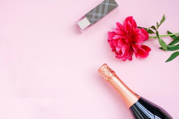 Ragazze di layout festivo, una bottiglia di champagne, cosmetici, peonia fiore rosso, vista dall'alto