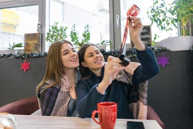 Ragazze di lifestyle di inverno in caffè divertendosi guardando i vecchi rotoli di film