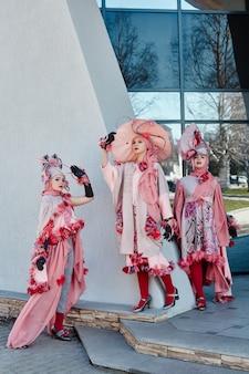 Ragazze di nuova moda vogue abiti creativi in posa per strada, abito e cappello rosa, abbigliamento etnico