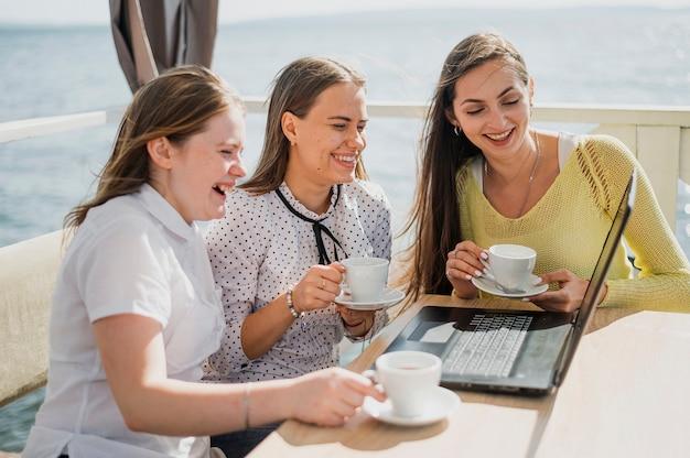 Ragazze di smiley di tiro medio con tazze e laptop