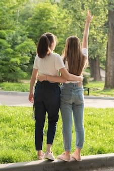 Ragazze di vista posteriore che posano nel parco