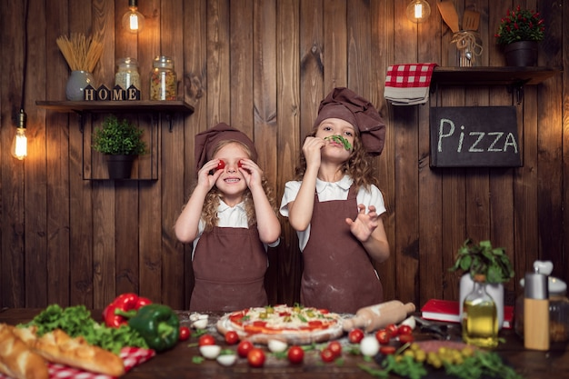 Ragazze divertenti che cucinano pizza e che imbrogliano con i pomodori e la lattuga
