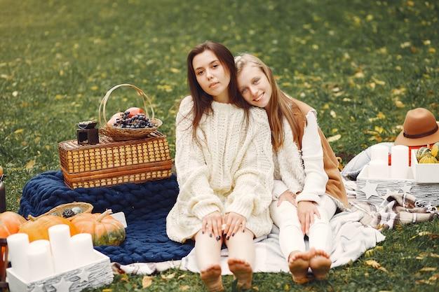 Ragazze eleganti e alla moda che si siedono in un parco di autunno
