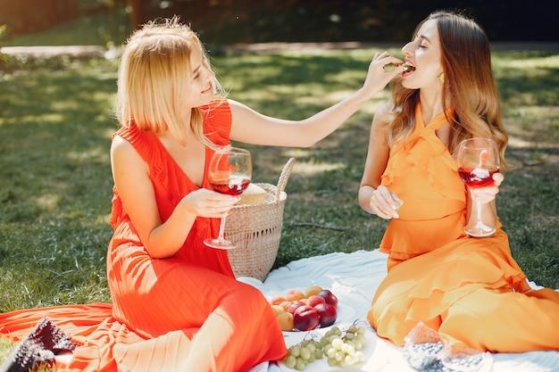 Ragazze eleganti e alla moda in un parco estivo
