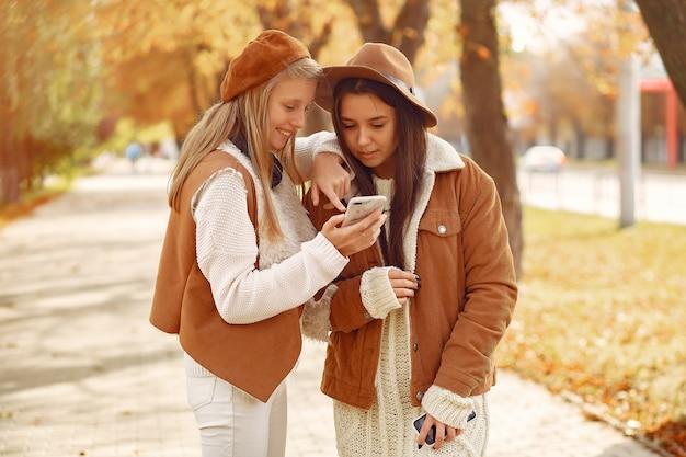 Ragazze eleganti e alla moda in un parco in autunno