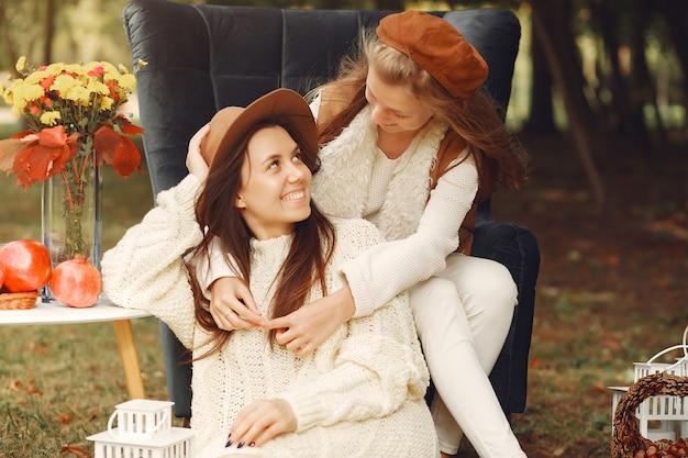 Ragazze eleganti e alla moda, seduto su una sedia in un parco